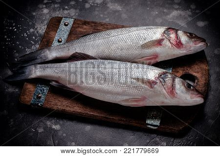 fresh raw sea bass fish on wooden cutting board cooking concept on a dark background