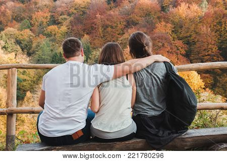 One guy hugs two girls looking at the autumn landscape