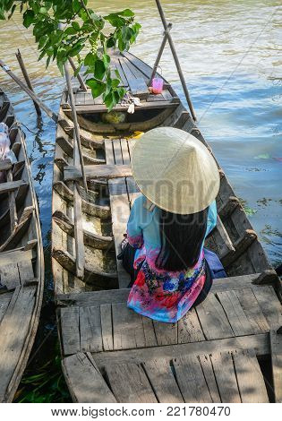 A Vietnamese woman in traditional dress sitting on wooden boat.