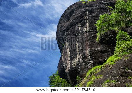 A monkey face in the rocky cliffs rising above the dahongpao cha, big red robe tea, area of wuyishan china in fujian province.