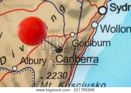 Close-up of a red pushpin in a map of Canberra, Australia.