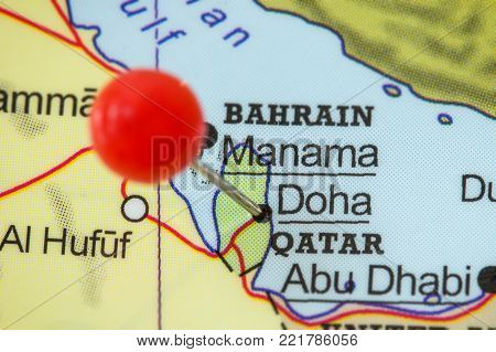 Close-up of a red pushpin in a map of Doha, Qatar.