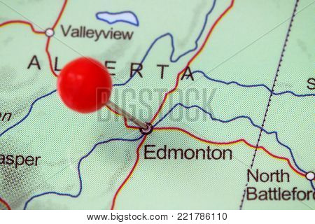 Close-up of a red pushpin in a map of Edmonton, Canada.
