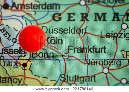 Close-up of a red pushpin on a map of Frankfurt, Germany.