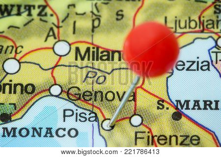 Close-up of a red pushpin in a map of Pisa, Italy.