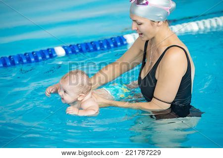 mother teach her baby, how to swim in a swimming pool
