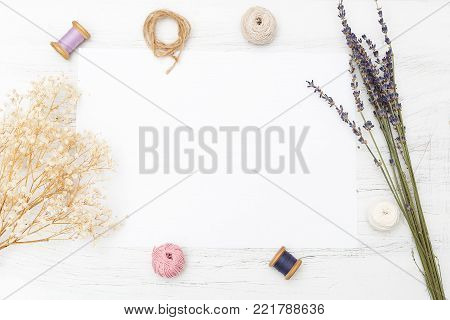 White blank card with flowers and ribbon on wooden background. Product mockup