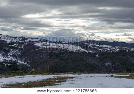 Majestic view of cloudy sky, winter mountain, snowy glade, residential district, conifer and deciduous forest   from Plana mountain toward Rila mountain, Bulgaria, Europe