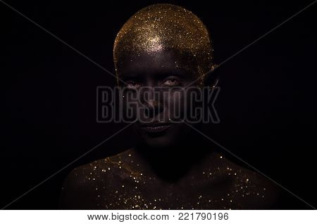 Portrait of a beautiful woman with creative body art glowing make up. Face is colored with black paint.