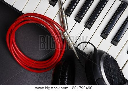 DJ Tools. Musical instruments close-up on black background. Synthesizer, headphones and cable. Midi keys and jack cable