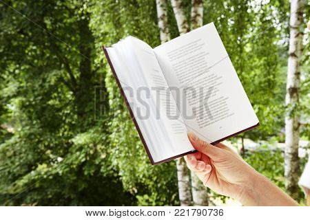 girl is holding book in nature close-up. A woman's hand with book. Hobby to read book