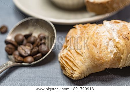 Sicilian puff pastry with coffee beans in a silver spoon