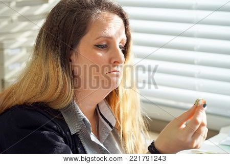 A blonde woman holding wedding engagement ring in hands, engaged girl doubts about marriage proposal, abandoned wife depressed after getting divorced, help to overcome breaking up, starting new life, close-up