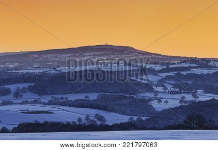 Yellow Sunset Sky Over Summit Of Brown Clee Hill In Shropshire Hills At Winter