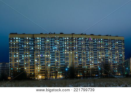 The new building in the night in the suburb of the big city. The view from the heath