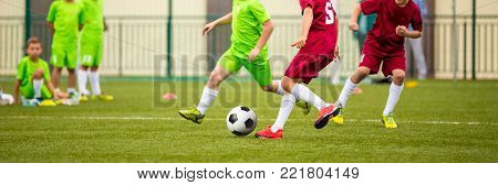 Boys Kicking Soccer Ball. Children Soccer Team. Kids Running with Ball on Football Pitch. Young Soccer Players in Action