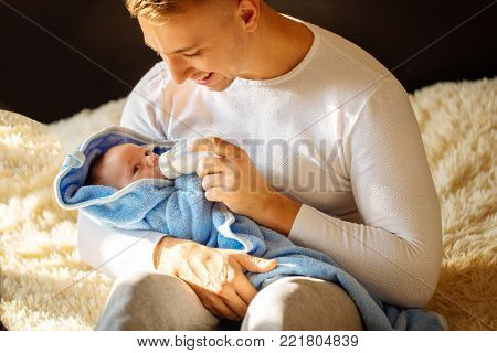 happy Father Feeding Newborn Baby At Home