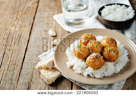 Baked Orange Chicken Meatballs with rice on a wood background