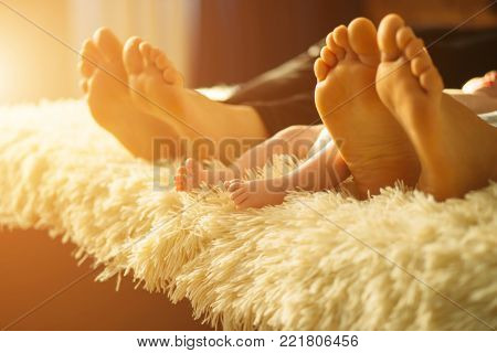 family laying on bed, their feets on focus. Mother, father and infant newborn baby son