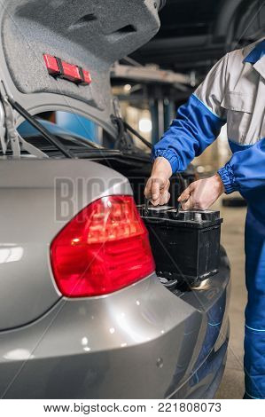 Engine engineer is replacing car battery because car battery is depleted. concept car maintenance.