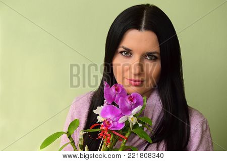 The beautiful young woman the brunette with green eyes and a pink orchid. The woman is dressed in a pink dress, has pink lips
