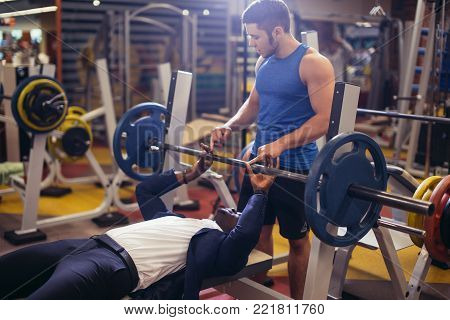 Personal trainer helping the man in the suit on bench press in gym. Fitness and gym