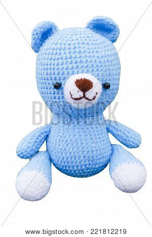 Crochet doll of lovely blue sky bear smiling face with two black eyes and brown nose, isolated white background and clipping path, hobby handmade work with yarn at home for woman