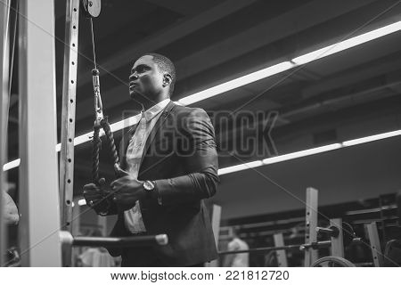 Exercise for triceps in gym. African bussinesman in classic suit performs an exercise on triceps in simulator. fitness in gym. black and white