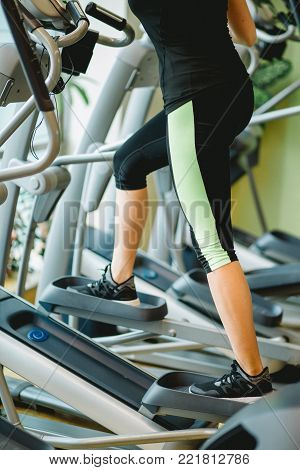 Young fit woman using an elliptic trainer in fitness center, listening music with headphones and smiling. Close up of legs of fitness girl in gym