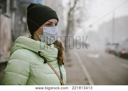 the girl is standing by the road in a protective medical mask. Dense smog in the streets of the city.