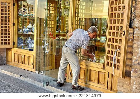 Isfahan, Iran - April 23, 2017: The trader washes the shop window in the china store, which is located on Naghshe Jahan Square.