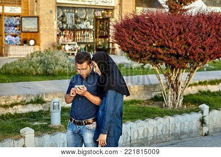 Isfahan, Iran - April 23, 2017: A young couple strolls along Naghsh E Jahan Square, and looks at something on the smartphone screen.