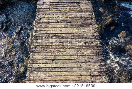Conceptual Image Of A Rickety Wooden Footbridge Over A Stream Or Creek Or Brook In Scotland