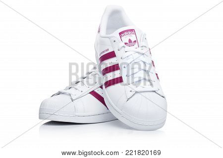 LONDON, UK - JANUARY 12, 2018: Adidas Originals Superstar red shoes on white background.German multinational corporation that designs and manufactures sports shoes, clothing and accessories.