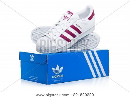 LONDON, UK - JANUARY 12, 2018: Adidas Originals Superstar red shoes with box on white background.German multinational corporation that designs and manufactures sports shoes, clothing and accessories.