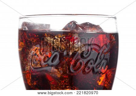 LONDON, UK - JANUARY 02, 2018: Original glass of Coca Cola drink on white background. The drink is produced and manufactured by The Coca-Cola Company.