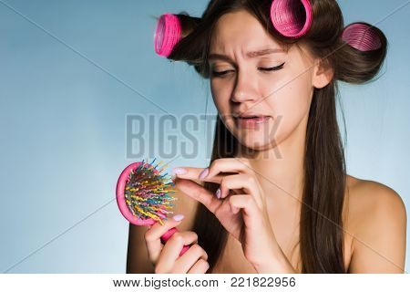 sad girl wants a stylish hairstyle, on the hair curler's head, a lot of hair in the hairbrush