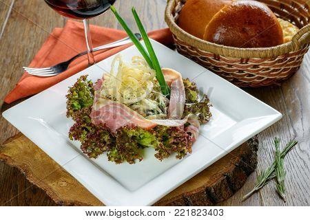 Ham salad and calamari garnished on white sqare plate