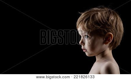 Profile portrait of four-year old boy over black background