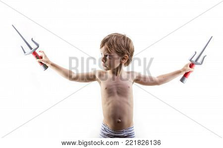 Young boy playing with two toy daggers over white