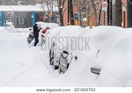 Montreal, CANADA - 13 January 2018: a man is shoveling snow to free his stuck car