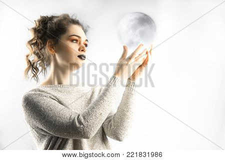 portrait of a beautiful caucasian curly hair young woman holds moon like transparent sphere in her hands, woman's cicle health concept.