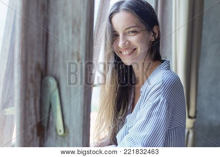 Indoor shot of amazing sophisticated young mixed raced woman wearing blue oversized shirt posing by window at light modern bedroom. Authentic lady looking at camera with cheerful pretty toothy smile.