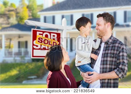 Young Mixed Race Caucasian and Chinese Family In Front of Sold For Sale Real Estate Sign and House.