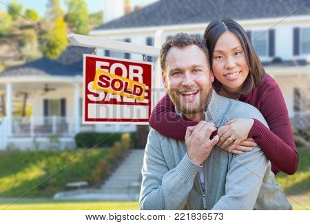 Mixed Race Caucasian and Chinese Couple In Front of Sold For Sale Real Estate Sign and House.
