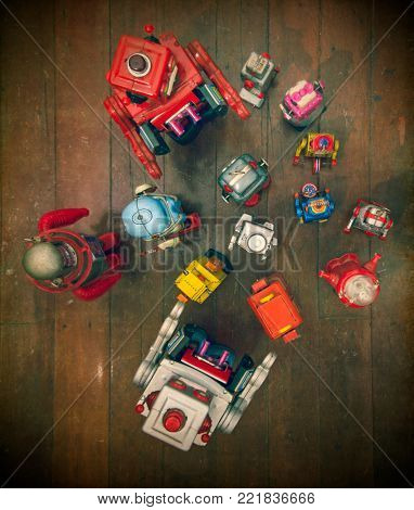 a large group of retro robots gather for a meeting on a old wooden floor