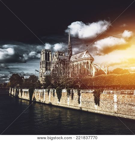Rear low-angle view of the right side of Notre-Dame de Paris cathedral against dramatic cloudy sky