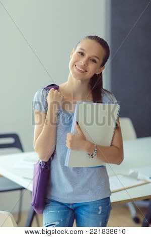 Portrait of young student woman holding exercise books. Student woman