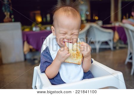 Cute little Asian 18 months / 1 year old toddler baby boy child biting & eating toast as breakfast in beautiful restaurant near garden at hotel, kid sitting on high feeding chair, self feeding concept