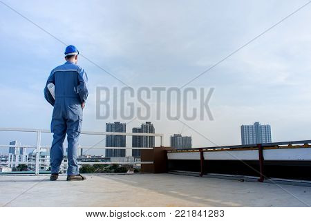 Professional Asian engineering wearing blue safety helmet holding blueprint standing on building deck,Industrial Workers concept
